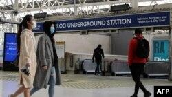 Orang-orang memakai masker wajah, yang direkomendasikan untuk dipakai di angkutan umum, di stasiun Waterloo di London, 11 Mei 2020. (Foto: AFP)