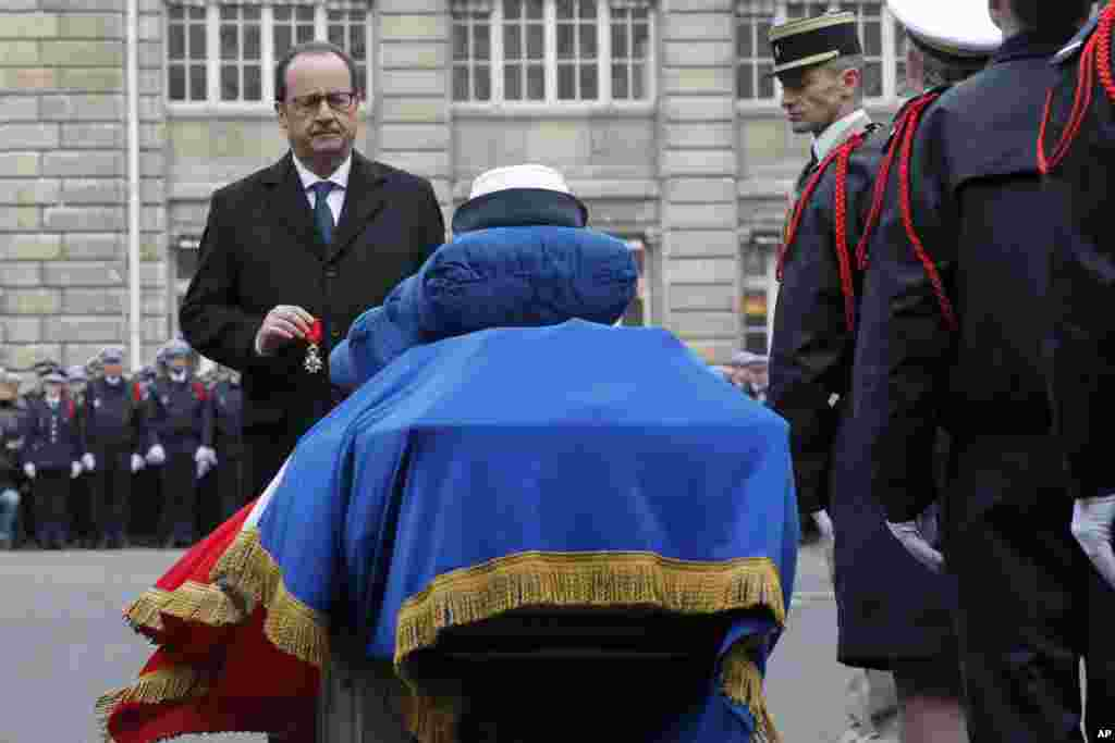 French President Francois Hollande holds a medal in front of the coffin of Police officer Clarissa Jean-Philippe during a ceremony to pay tribute to the three police officers killed in the attacks, in Paris, France, Jan. 13, 2015.