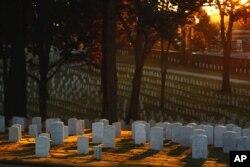 The sun rises over tombstones in the Marietta National Military Cemetery on Veteran's day, Nov. 11, in Marietta, Ga. (AP Photo/David Goldman)