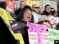 Internal Revenue Service employee Mary Maldonado, of Dracut, Mass., center, displays a placard during a rally by federal employees and supporters, Jan. 17, 2019, in front of the Statehouse, in Boston, held to call for an end of the partial shutdown.