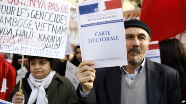"Turkish citizens in France, one of them holding a booklet reading ""Electoral card"", demonstrate in front of the Senate to protest against a law that would make it a crime to deny ""genocide"" of Armenians, in Paris, Monday, Jan. 23, 2012."