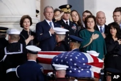 El expresidente George W. Bush, su esposa Laura Bush (izquierda), y otros miembros de la familia observan como el ataúd del ex presidente George H.W. Bush, cubierto por la bandera, es transportado por una guardia de honor militar de servicios conjuntos para permanecer en capilla ardiente en la Rotonda del Capitolio de EE.UU., el 3 de diciembre de 2018.