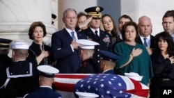Former President George W. Bush, Laura Bush, left, and other family members watch as the flag-draped casket of former President George H.W. Bush is carried by a joint services military honor guard to lie in state in the rotunda of the U.S. Capitol, Dec. 3