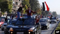 Syrian government supporters wave national flags and chant slogans against U.S. President Trump during demonstrations following a wave of U.S., British and French military strikes to punish President Bashar Assad for suspected chemical attack against civi