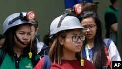 Office workers wear protective gear as they evacuate their building after an earthquake was felt in Manila, Philippines, Aug. 11, 2017. Office workers in the capital left their buildings but no damage was apparent after the quake struck about midday Friday.
