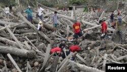 Tim SAR dan relawan mengangkat mayat korban topan Bopha yang tertindih tumpukan kayu yang terbawa arus banjir bandang di kota New Bataan, Lembah Compostela,Filipina (7/12).