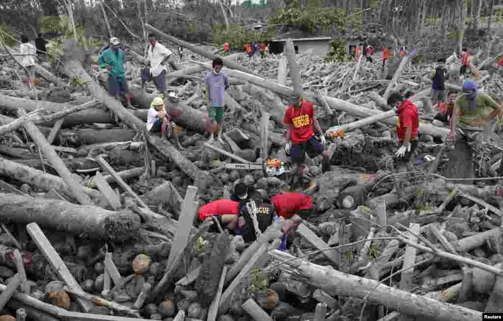 Rescuers recover a body of a typhoon victim from debris swept by floodwaters at the height of Typhoon Bopha in New Bataan town in Compostela Valley, Philippines, December 7, 2012.