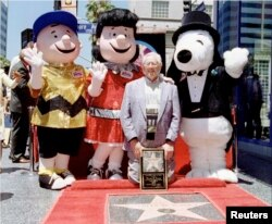 """Charles M. Schulz, character creator """"Peanuts"""", posing with (L-R) Charlie Brown, Lucy and Snoopy on June 28, 1996 (Photo: Reuters)"""