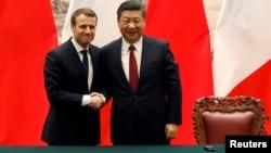 法国总统马克龙与中国国家主席习近平在北京举行联合记者会后握手。(2017年1月9日)