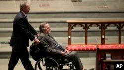 前总统小布什推着坐在轮椅上的父亲、前总统老布什抵达休斯顿的圣马丁圣公会教堂,参加前第一夫人芭芭拉·布什的葬礼仪式。(2018年4月21日)
