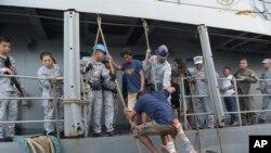 与中国渔船相撞落水的菲律宾渔民被另一艘船救起返回海岸。(2019年6月14日)