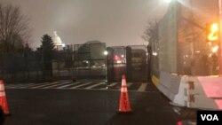 资料照片:夜幕降临被高高的围栏所远远环绕的国会山。(2021年2月15日)
