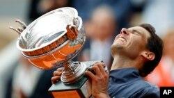 El español Rafael Nadal levanta la copa después de derrotar al austríaco Dominic Thiem en el partido final de hombres del Abierto de Francia en el estadio Roland Garros, en París. Domingo, 9 de junio de 2019. Nadal ganó 6-3, 5-7, 6-1, 6-1. (AP Photo/Pavel Golovkin)