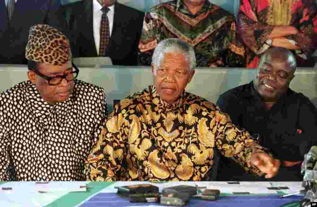Le président sud-africain Nelson Mandela, au centre, médiateur de la crise congolaise anime une conférence de presse avec le président zaïrois Mobutu Sese Seko et le chef rebelle Laurent-Désiré Kabila, à bord du SAS Outeniqua dans le port de Pointe Noire.