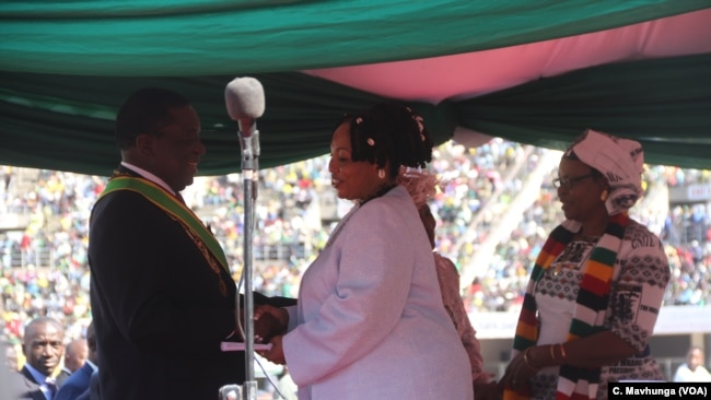 FILE - Priscilla Chigumba, right, head of Zimbabwe Electoral Commission, talks with President Emmerson Mnangagwa in Harare, Aug. 26, 2018.