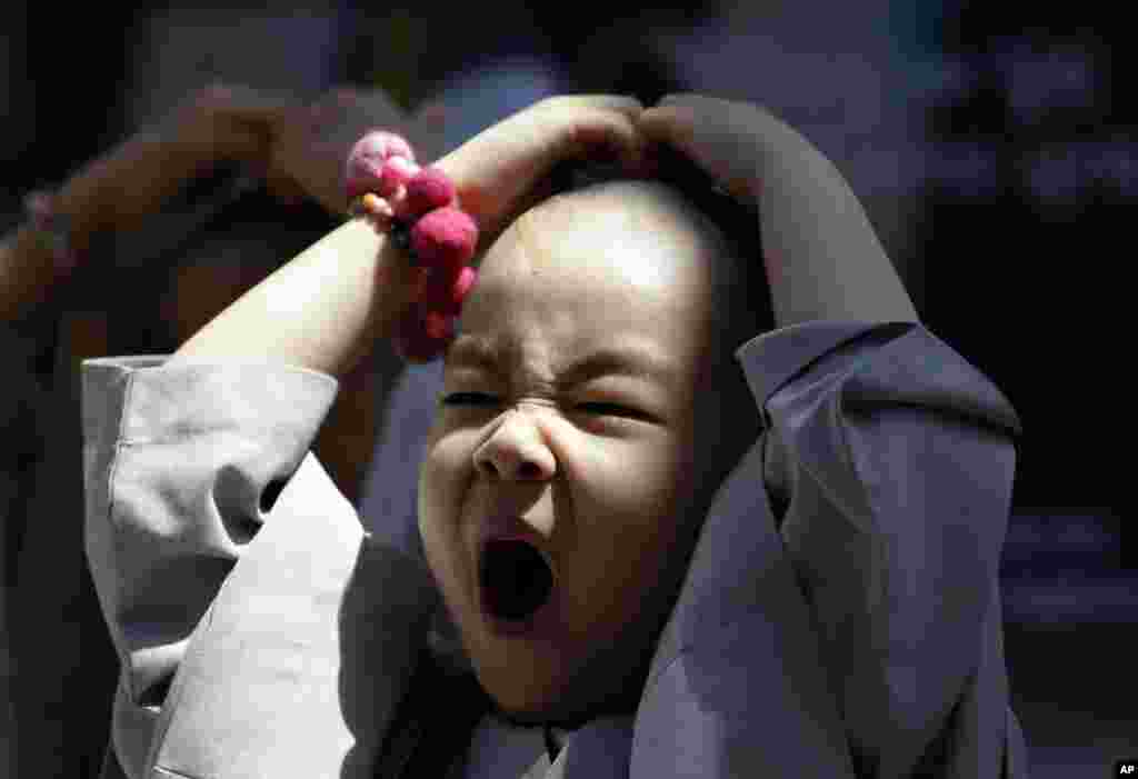 A shaven-headed young boy, who was among ten children who entered a temple to have an experience of monks' life for three weeks, yawns while attending a volunteer activity in Seoul, South Korea.