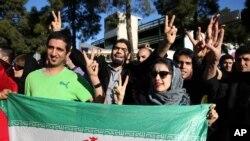 Warga Iran menanti kedatangan Menteri Luar Negeri Mohammad Javad Zarif yang kembali dari Lausanne, Swiss sembari mengacungkan tanda kemenangan atas kesepakatan nuklir, Jumat (3/4).