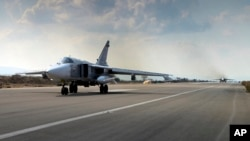 FILE - In this photo taken from Russian Defense Ministry official website on Oct. 6, 2015, a Russian SU-24M jet fighter prepares to take off from an airbase in Syria.