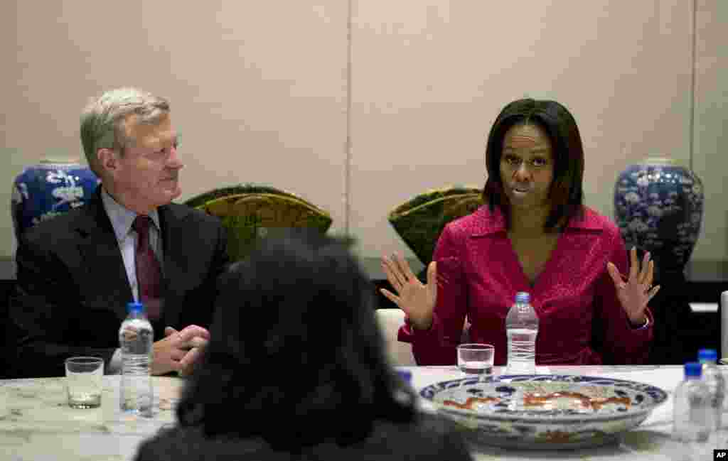 U.S. first lady Michelle Obama speaks next to U.S. Ambassador to China Max Baucus as they attend a round table discussion on education at the U.S. Embassy in Beijing, March 23, 2014.