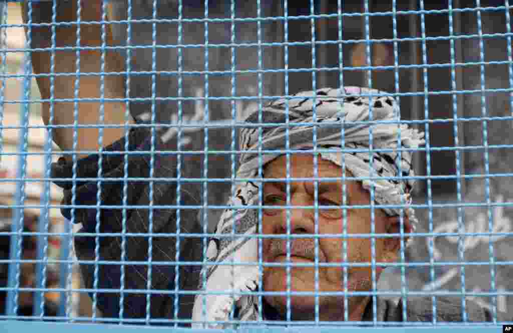 A Palestinian man stands in a symbolic prison cell during a protest supporting Palestinian inmates on hunger strike in Israeli jails, in the West Bank city of Ramallah, May 14, 2012.