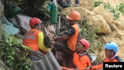 Rescuers pull out a survivor from rubble after a landslide in the city of Naga, Cebu island, Philippines, Sept. 20, 2018.