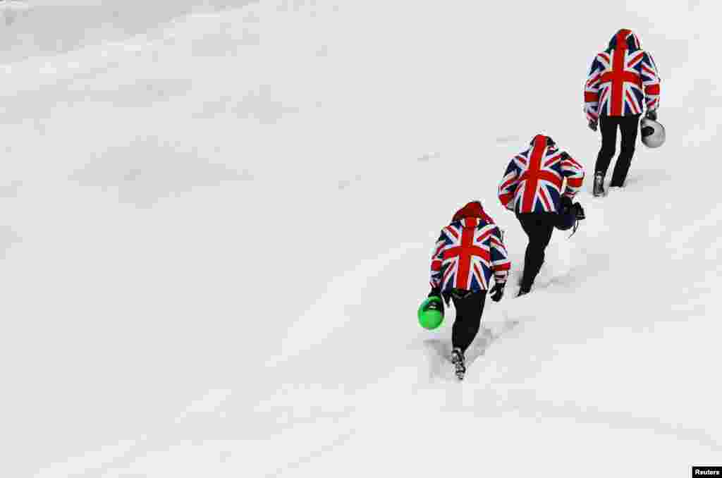 Three riders wear jackets with the design of the British Union Jack as the walk to the upper start position of the natural ice run of the Cresta Run during the International Match skeleton competition at the private St. Moritz Tobogganing Club (SMTC), Switzerland.