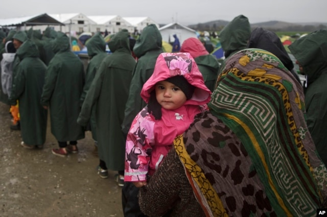A migrant holds her child as she queues for food portions at the Greek border camp near Idomeni, March 10, 2016.