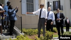 U.S. President Barack Obama, with New Orleans Mayor Mitch Landrieu at his back, chats with residents in a part of the Louisiana city reconstructed after Hurricane Katrina, Aug. 27, 2015.