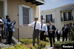 FILE - U.S. President Barack Obama chats with local residents in an area reconstructed after Hurricane Katrina, in New Orleans, La., Aug. 27, 2015. At his side is New Orleans Mayor Mitch Landrieu.