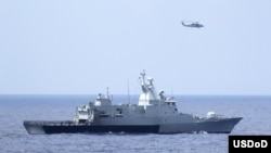 The Royal Malaysian Navy corvette KD Terengganu and a U.S. Navy MH-60R Sea Hawk helicopter conduct a coordinated air and sea search for a missing Malaysian Airlines jet in the Gulf of Thailand, March 12, 2014. (U.S. Navy photo by Operations Specialist 1st Class Claudia Franco)