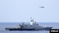 3月12日美国海军直升机与马来西亚海军配合搜寻失踪的马航370班机(图片由美国海军提供)