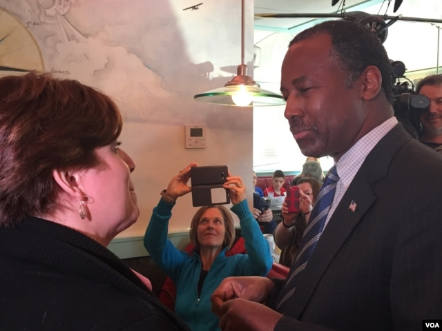 Presidential candidate Ben Carson talks with a woman at the Airport Diner in Manchester, New Hampshire, Feb. 7, 2016. (K. Gypson/VOA)