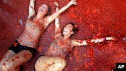 "Two woman lie in a puddle of squashed tomatoes during the annual ""tomatina"" tomato fight fiesta, in the village of Bunol, 50 kilometers outside Valencia, Spain, Wednesday, Aug. 26, 2015."