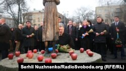 In central Kyiv on Nov. 25, 2017, President Petro Poroshenko and hundreds of other people lay symbolic wheat ears and light candles before the monument commemorating victims of the famine.