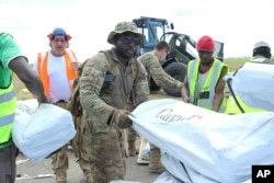 Members of the US army help load supplies at Beira International airport, Mozambique, Monday, April 1, 2019, joining the humanitarian aid efforts following a cyclone that hit the country on March 14.