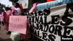 Mwanamke akiwa na bango la kutetea wahamiaji nje ya ubalozi wa Marekani, Mexico City.