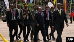 ប្រធានាធិបតីប្រទេសស៊ូដង់ Omar al-Bashir (កណ្ដាល) ដើរក្នុងពិធីកាន់តំណែងរបស់ប្រធានាធិបតីអ៊ូហ្គង់ដា Yoweri Museveni ដែលបានជាប់ឆ្នោតសាជាថ្មី កាលពីថ្ងៃទី១២ ខែឧសភា ឆ្នាំ២០១៦ នៅទីក្រុងកាំប៉ាឡា។