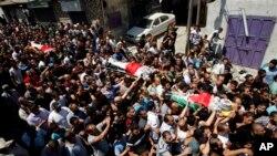 Pelayat Palestina membawa jenazah tiga warga Palestina yang terbunuh ke tempat pemakaman mereka di kamp pengungsi Qalandia, di pinggiran kota Ramallah, Tepi Barat, Senin (26/8).