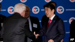 Japanese Prime Minister Shinzo Abe is greeted by U.S. Chamber of Commerce President and CEO Tom Donohue, left, as he arrives at a meeting at chamber offices in Washington, April 29, 2015.