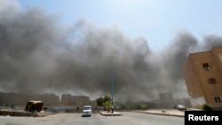 Smoke rises after what activists say was shelling from forces loyal to Syria's President Bashar al-Assad in Raqqa, Aug. 17, 2014.