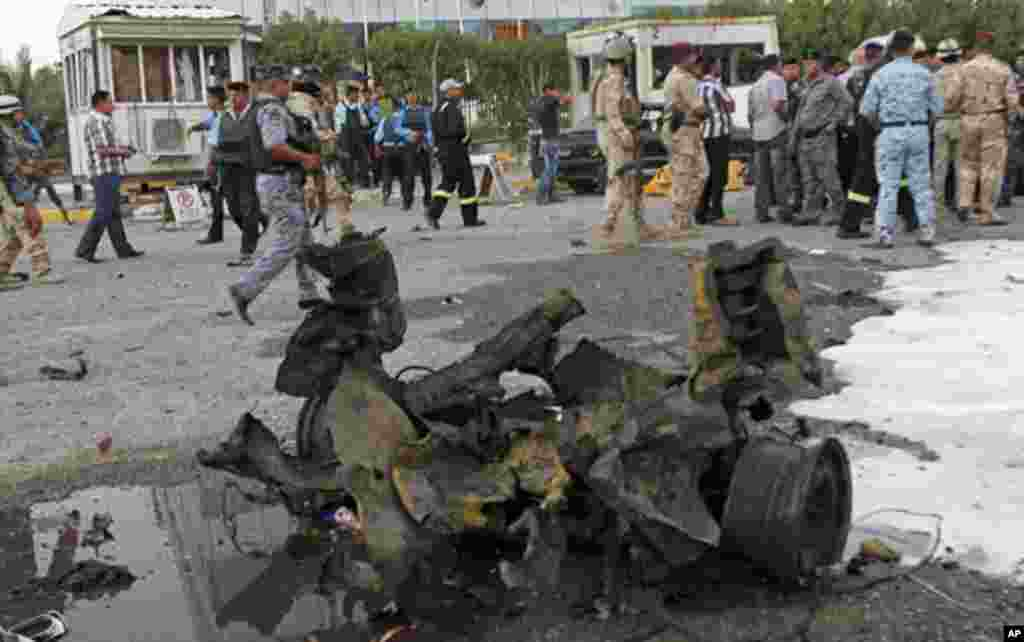 People and security forces inspect the scene of a car bomb attack in Basra, 340 miles (550 kilometers) southeast of Baghdad, Iraq, July 2, 2013.