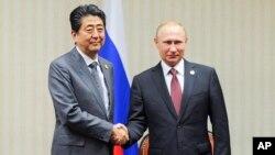 PM Jepang Shinzo Abe (kiri) dan Presiden Rusia Vladimir Putin dalam pertemuan di sela KTT APEC di Lima, Peru, 20 November lalu (foto: dok).
