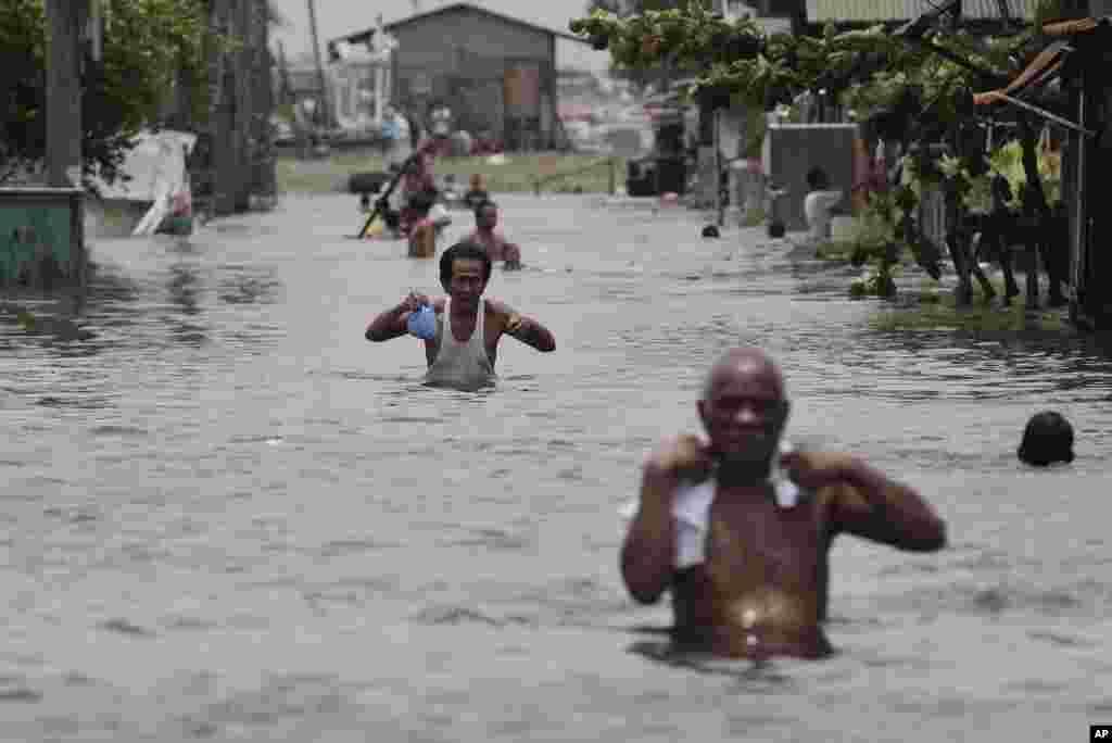 Dân Philippines bước cẩn thận trong nước lụt tới ngực tại phía bắc thủ đô Manila, 1/8/2012.