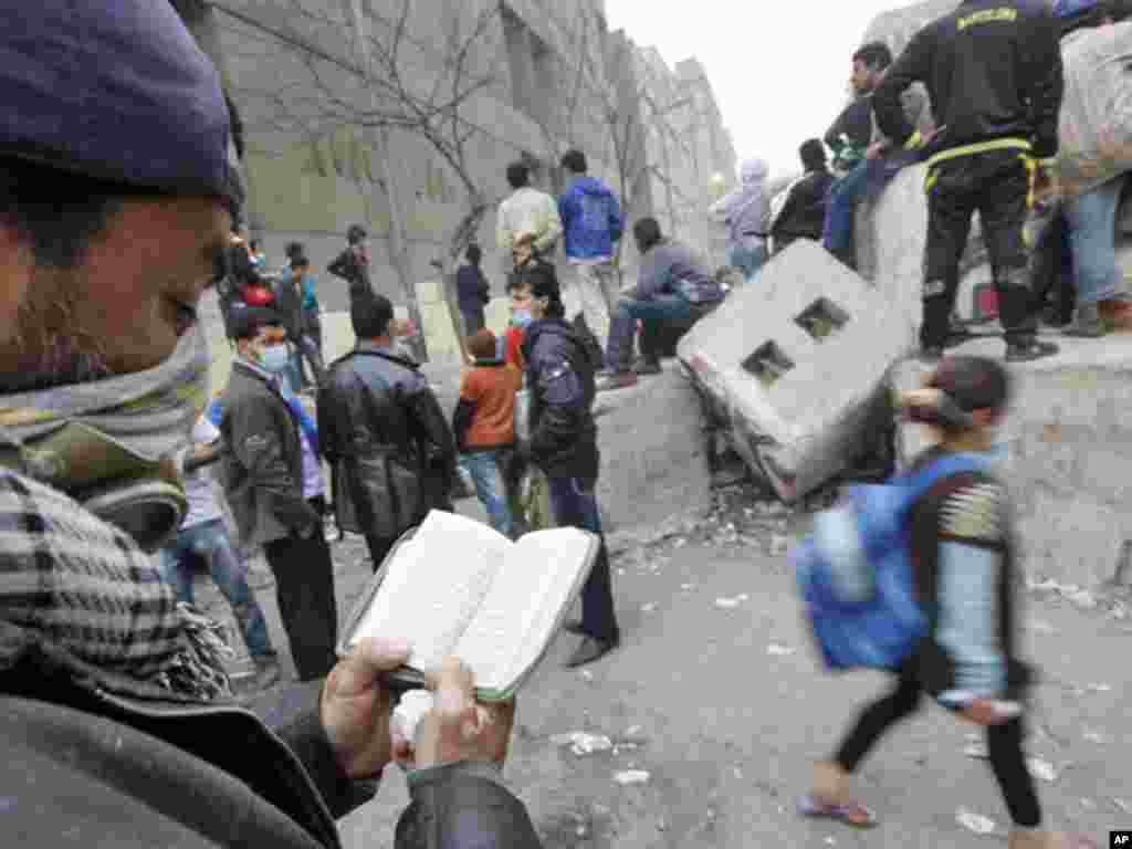 A protester reads the Koran during clashes with security forces near the Interior Ministry in Cairo, February 6, 2012. (Reuters)