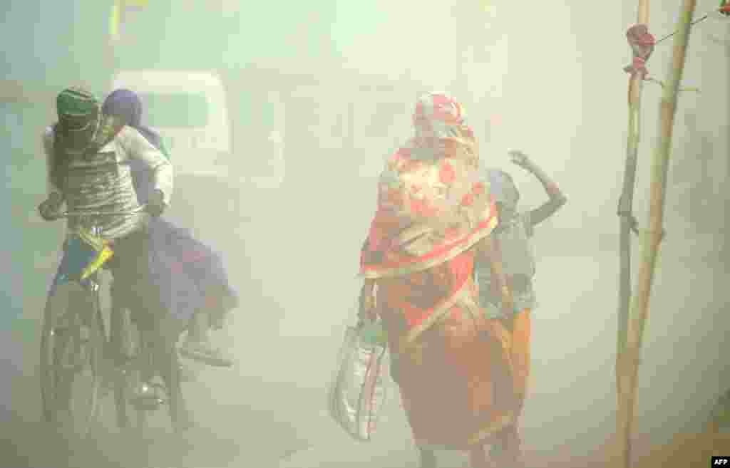 Pedestrians and cyclists travel through a dust storm at the Sangam, the confluence of the rivers Ganges, Yamuna and mythical Saraswati in Allahabad, India.