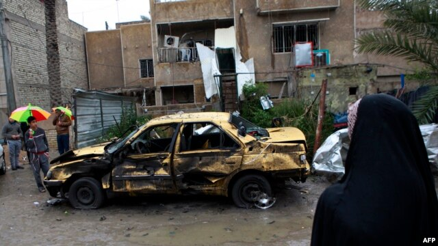 Local residents gather at the site of a car bomb explosion in the Hurriyah neighborhood of Baghdad, Feb. 3, 2014.