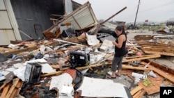 """颶風""""哈維""""過後,德克薩斯凱迪的一名婦女查看房屋受損情況。 (2017年8月26日)"""