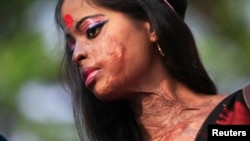 Hasina, a survivor of an acid attack, takes part in an awareness rally about the violence against women...