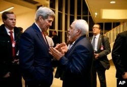 FILE - Secretary of State John Kerry talks with Iranian Foreign Minister Mohammad Javad Zarif in Vienna, after the International Atomic Energy Agency (IAEA) verified that Iran has met all conditions under the nuclear deal.