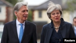 FILE - Britain's Prime Minister Theresa May and Chancellor of the Exchequer Philip Hammond visit a home near the Conservative Party's conference in Manchester, Oct. 2, 2017.